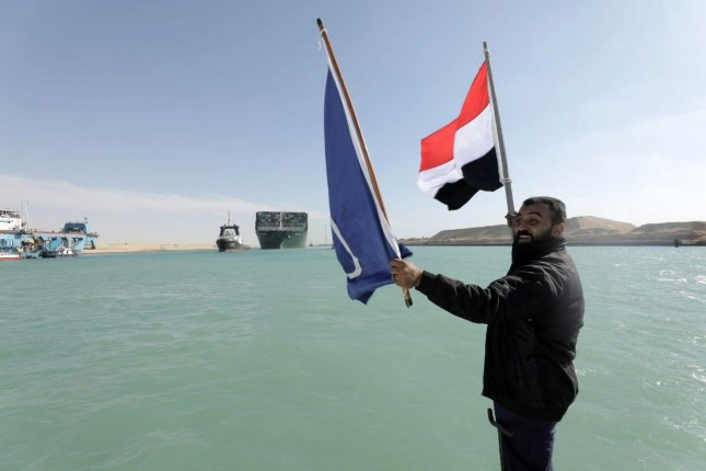 A worker waves the Egyptian flag as the Ever Given after it was fully freed and floated in the Suez Canal in March 29. The ship has been released from detention after a settlement between its owner and the Suez Canal Authority was reached. File Photo by Suez Canal Authority Office/UPI