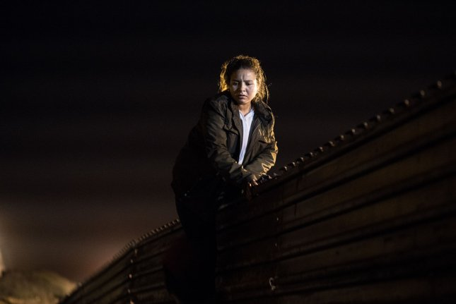 A migrant from Honduras climbs a section of border fence in Tijuana, Mexico, on December 26, 2018. Photo by Ariana Drehsler/UPI