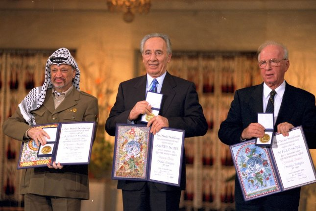Palestinian leader Yasser Arafat (L), Israeli Foreign Minister Shimon Peres (C) and Prime Minister Yitzhak Rabin hold the Nobel Peace Prize in Oslo, Norway, on December 10, 1994. File Photo by Israeli Government Press Office