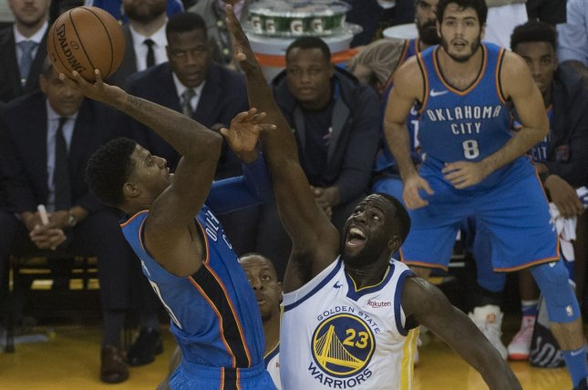 Oklahoma City Thunder forward Paul George (L) shoots over Golden State Warriors forward Draymond Green (23) in the second quarter on October 16, 2018 at Oracle Arena in Oakland, California. Photo by Terry Schmitt/UPI