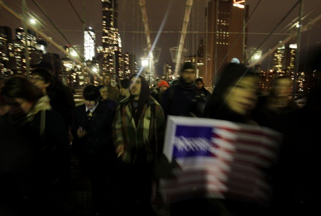 Occupy Wall Street Protesters hold signs as they cross the Brooklyn Bridge after a rally in Foley Square In New York City on November 17, 2011. Multiple protests took place in Manhattan throughout the day on the 60 day anniversary of the Occupy Wall Street Movement. UPI/John Angelillo