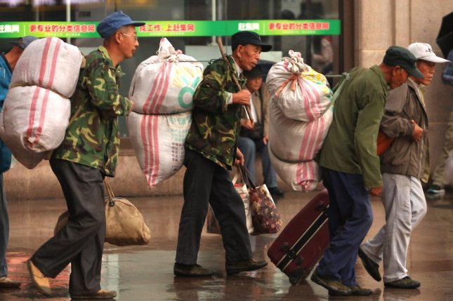 Chinese holiday travelers head to a central train station in September 2015 in Beijing. This week, hundreds of thousands of Chinese migrants returning home from the southern city of Guangzhou were stranded due to heavy snow in central China. File Photo by Stephen Shaver/UPI