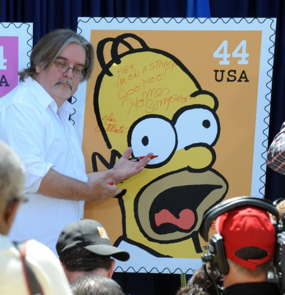 Creator and Executive Producer Matt Groening signs a poster at the unveiling of the new The Simpsons U.S. postage stamps in Los Angeles May 7, 2009. (UPI Photo/Jim Ruymen)