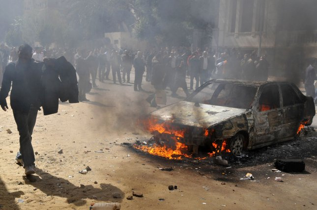 A burning car is seen as Egyptian police officers protests in downtown Cairo, Egypt, February 23, 2011. UPI