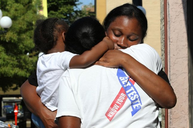 Finesse McNichols, sister of slain mass shooting victim Thomas TJ McNichols, is comforted by friends at a memorial near the scene of the crime on Monday in Dayton, Ohio. Photo by John Sommers II