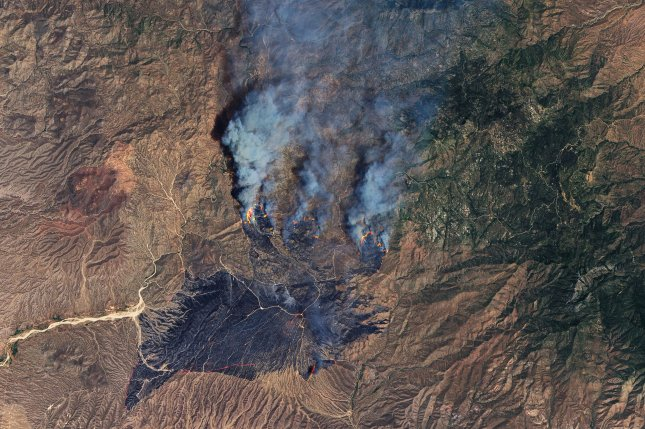 A vehicle fire near the intersection of Bush Highway and State Route 87 ignited the brush and grass nearby in Phoenix on June 13. Three days later nearly 65,000 acres northeast of Phoenix had burned. Photo by NASA/UPI