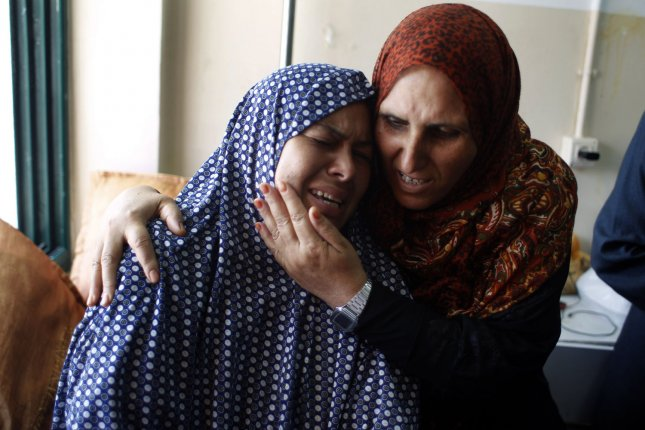 Mother (L) of three-year-old Mouid al-Araj, mourns during his funeral in Khan Yunis, in the southern Gaza on July 13, 2014. Israeli strikes on Gaza killed a teenager and a woman, medics said, raising the overall death toll to 166 as the punishing air campaign entered its sixth day. UPI/Ismael Mohamad