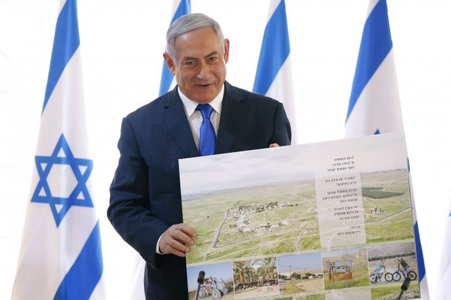 Israeli Prime Minister Benjamin Netanyahu holds up a placard given to him as a gift from Israeli residents of the area, at the start of a weekly cabinet meeting in the Jordan Valley, in the Israeli-occupied West Bank. Pool photo by Amir Cohen/UPI