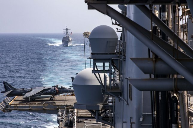 The Arleigh Burke-class guided-missile destroyer USS Bainbridge (DDG 96) steams behind the Wasp-class amphibious assault ship USS Kearsarge (LHD 3) in this May file photo. The US Navy has just awarded BAE Systems a contract to maintain AEGIS guided-missile destroyers. Photo by MC2 Ryre Arciaga/U.S. Navy/UPI