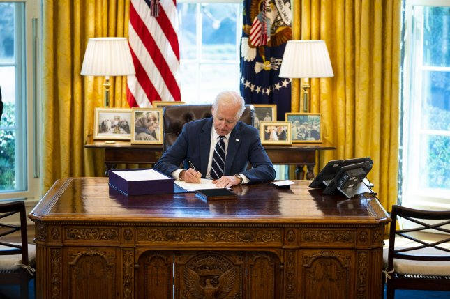 President Joe Biden signs the $1.9 trillion American Rescue Plan on in the Oval Office of the White House in Washington, D.C., on March 11. The measure, among other things, sent tens of millions of Americans new economic stimulus payments. File Pool Photo by Doug Mills/UPI