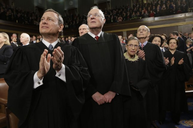 Chief Justice John Roberts, on left, listens with the other justices to President Barack Obama's State of the Union address on Feb. 12, 2103. Roberts wrote the majority opinion in June freeing states from the Voting Rights Act. -- UPI/Charles Dharapak/Pool