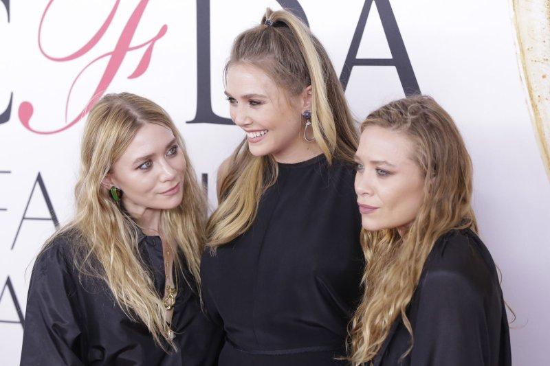 Ashley Olsen (R) with sisters Mary-Kate Olsen (L) and Elizabeth Olsen at the CFDA Fashion Awards on June 6. File Photo by John Angelillo/UPI