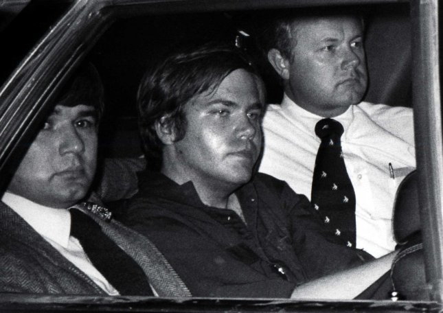 John Hinckley Jr. is flanked by federal agents as he is driven away from court in Washington, April 10, 1981. UPI Files.