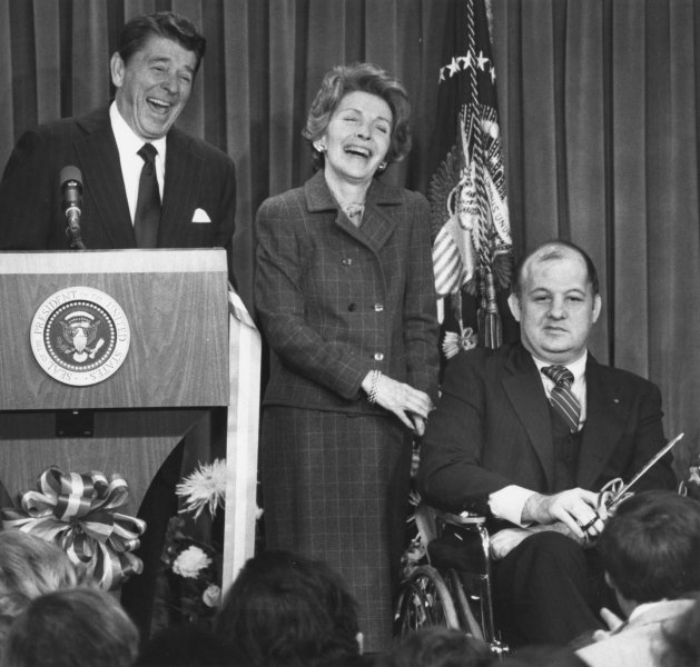 President Ronald and First Lady Nancy Reagan and Press Secretary James Brady joke with reporters at the opening of the newly refurbished White House Press Room on November 9, 1981, eight months after Reagan and Brady were shot. (UPI Photo/Mal Langsdon/Files)