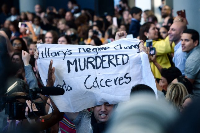 Protesters hold up a banner claiming Democratic presidential candidate Hillary Clinton is responsible for the murder of leading Honduran environmental activist Berta Cáceres. Clinton was discussing her economic policies at Southwest College in Los Angeles on Saturday. Photo by Jim Ruymen/UPI