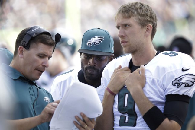 2916d8d1 Former Philadelphia Eagles quarterback Michael Vick (C) and Eagles QB Nick  Foles (R) go over plays during NFL action against the San Diego Chargers at  ...