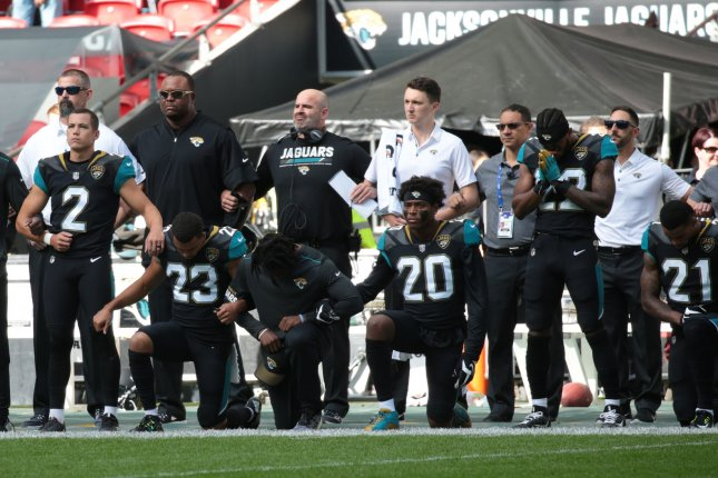 Jacksonville Jaguars team members crouch down and kneel during the American national anthem in defiance of President Trump remarks in the NFL International Series match against the Baltimore Ravens on September 24 at Wembley Stadium in London, England. Photo by Hugo Philpott/UPI