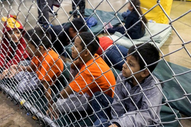 Detained children sit on pads behind cyclone fencing at the Central Processing Center in McAllen, Texas on July 13. File Photo courtesy of U.S. Rep. Doris Matsui's office/UPI