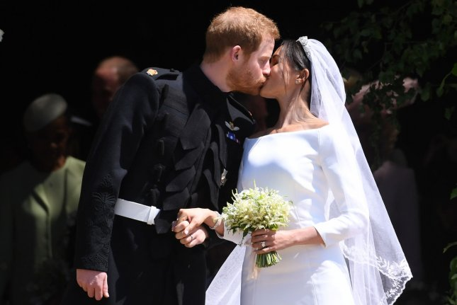 Britain's Prince Harry (L), duke of Sussex, and Meghan Markle, duchess of Sussex, kiss as they exit St. George's Chapel in Windsor Castle after their royal wedding ceremony on May 19, 2018.  File Pool Photo by Neil Hall/UPI