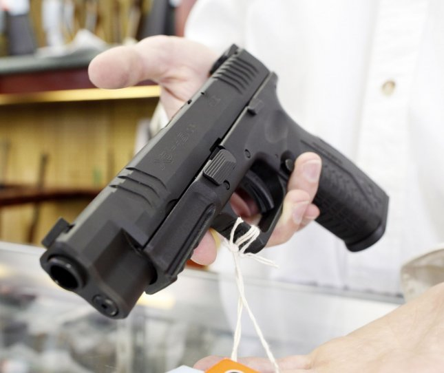 Greg Tropino Jr. displays a popular semiautomatic pistol manufactured by Springfield Armory at G. A. T. Guns in Dundee, Illinois on June 28, 2010. UPI/Brian Kersey