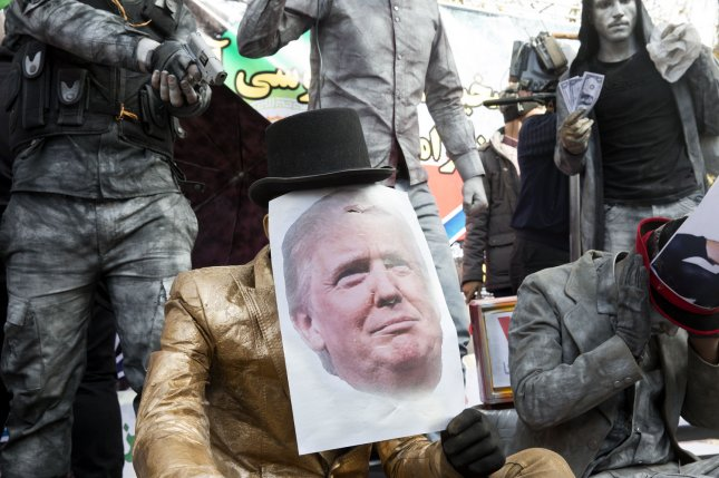 An Iranian demonstrator wears a picture of U.S President Donald Trump as the other one holds a gun on him during the 39th anniversary of the 1979 U.S. embassy takeover in front of the former diplomatic complex in Tehran on Sunday. Photo by Maryam Rahmanian/UPI