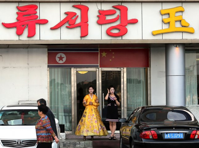File photo of a North Korean woman and hostess stand outside a North Korean restaurant waiting for customers in Dandong, China's largest border city with North Korea, in Liaoning Province, on May 30, 2015.  File photo by Stephen Shaver/UPI