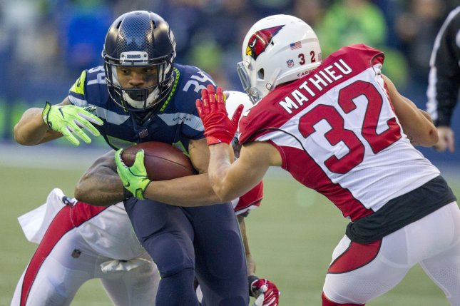 Ex-Seattle Seahawks running back Thomas Rawls (34) is tackled by Arizona Cardinals inside linebacker Deone Bucannon (20) and former free safety Tyrann Mathieu (32) after a 12-yard gain during the third quarter on December 31, 2017 at CenturyLink Field in Seattle, Washington. Photo by Jim Bryant/UPI