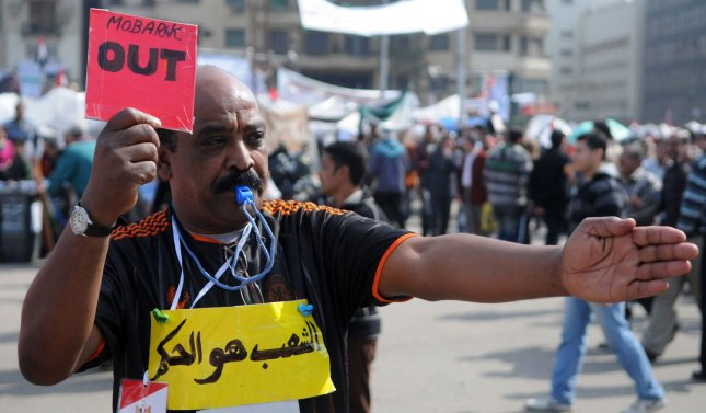 A Egyptian anti-government demonstrator hold up a red card that says Mubarak out during protest in Cairo's Tahrir Square in Egypt on February 9, 2011, the 16th day of consecutive protests calling for the ouster of President Hosni Mubarak. The sign on his chest reads The People. UPI