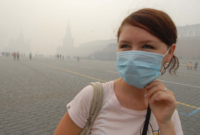 A woman wearing protective mask walks on Red Square through a heavy smog in Moscow on August 6, 2010. Russian capital was blanketed in record thick smoke causing by temperatures up to 100 F (38 C) and several days of nearby forest and peat fires. UPI/Alex Volgin