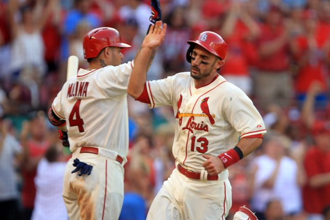 St. Louis Cardinals Matt Carpenter slaps hands with Yadier Molina, crossing home plate with the go-ahead run in the eighth inning against the Philadelphia Phillies at Busch Stadium in St. Louis on June 21, 2014. St. Louis won the game 4-1. UPI/Bill Greenblatt