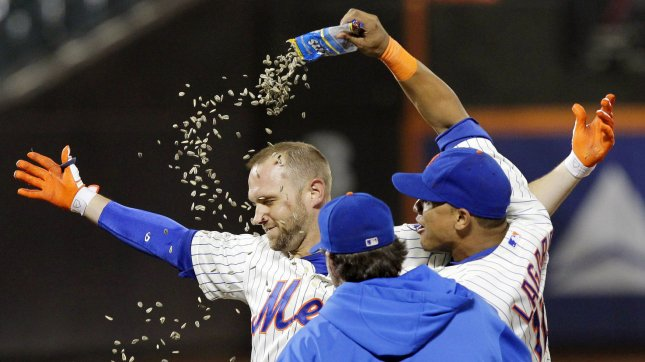 New York Mets Juan Lagares dumps sunflower seeds on Andrew Brown after Brown drives in the game winning runs with a single in the 13th inning against the Arizona Diamondbacks at Citi Field in New York City on July 1, 2013. The Mets defeated the Diamondbacks 5-4 in 13 innings. UPI/John Angelillo