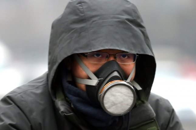 A Chinese man wears a heavy-duty air mask as he cycles through hazardous pollution hanging over Beijing. China's emissions far exceed that of the United States. According to the World Bank, Asia's largest economy produced 11 billion tons of carbon pollutants in 2013 – twice that of the United States' 5.8 billion tons. Photo by Stephen Shaver/UPI