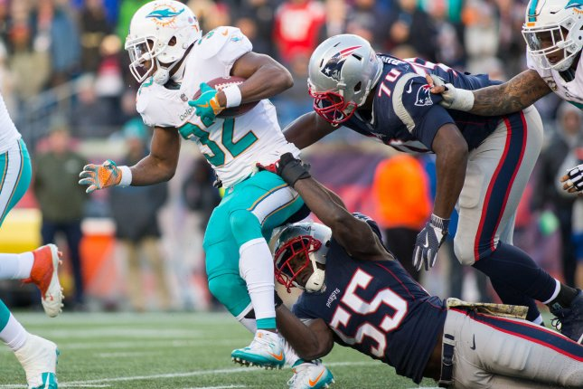 Miami Dolphins running back Kenyan Drake (32) is dragged down by New England Patriots linebacker defensive end Cassius Marsh (55) and defensive lineman Adam Butler (70) in the third quarter on November 26 at Gillette Stadium in Foxborough, Mass. Photo by Matthew Healey/UPI