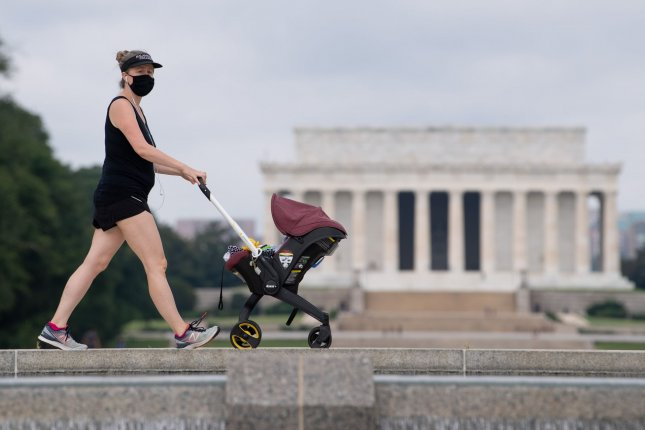 A masked woman pushes a stroller near the Lincoln Memorial on the National Mall in Washington, D.C., on September 2. Photo by Kevin Dietsch/UPI