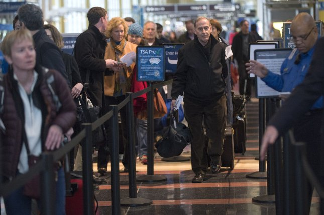 Travelers wait in a security checkpoint line at Ronald Reagan National airport, November 26, 2013, in Arlington, Virginia. (UPI/Kevin Dietsch)