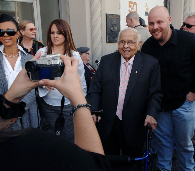 Honorary mayor of Hollywood Johnny Grant (C) smiles as a fan takes his picture in this November 29, 2007 file photo. Grant, best known for his role in hosting Hollywood Walk of Fame ceremonies, died on January 9, 2008, according to local media. He was 84. (UPI Photo/Jim Ruymen/file photo)