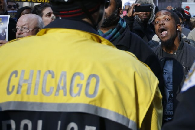 A demonstrator confronts a police officer while protesting after Chicago Mayor Rahm Emanuel addressed the City Council about the recent troubles with the Chicago Police Department, December 9, 2015. This week, Illinois Rep. Bobby Rush introduced a resolution in the House calling for a select committee to investigate recent and controversial police officer-involved shootings in the United States. Photo by Kamil Krzaczynski/UPI