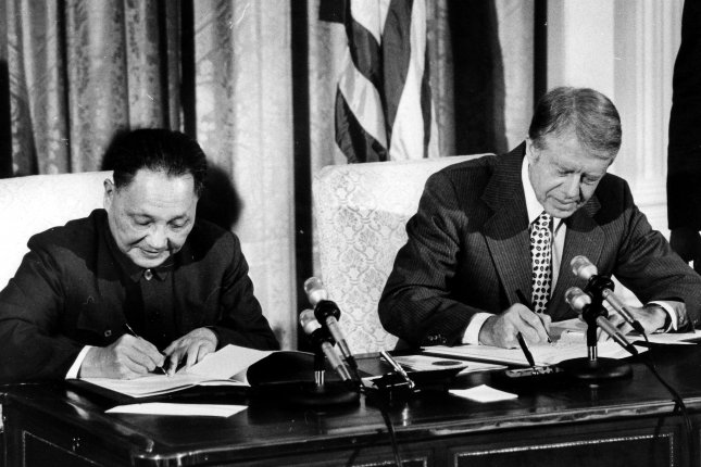 President Jimmy Carter and Chinese Vice Premier Deng Xiaoping sign an agreement at the White House which will open the way for future exchanges of science, technology and trade between the United States and the People's Republic of China.