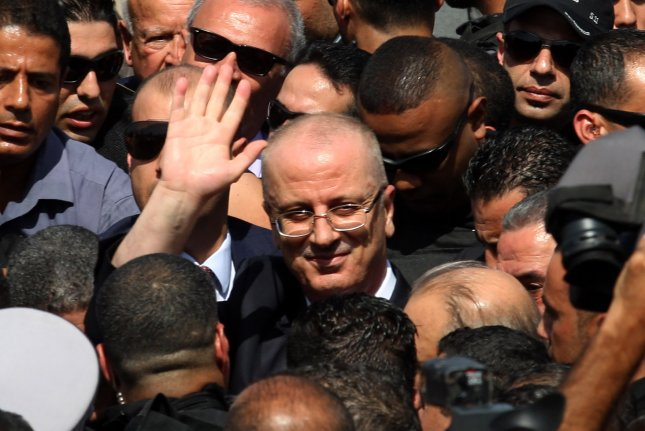 Palestinian Prime Minister Rami Hamdallah is surrounded by security as he waves following his arrival at the Erez border crossing in Beit Hanun in the northern Gaza Strip on Monday. Hamdallah is on on his first visit to the Gaza Strip for talks aimed at securing a rapprochement between Fatah and the enclave's rulers Hamas. Photo by Ismael Mohamad/ UPI