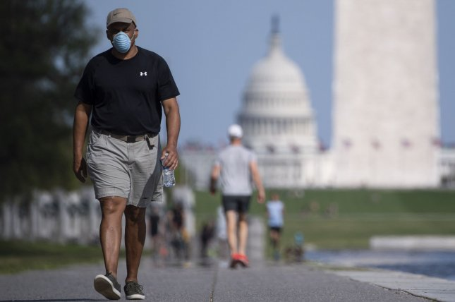 People enjoy the warm weather on the National Mall during the Coronavirus pandemic in Washington, D.C on Wednesday. Photo by Kevin Dietsch/UPI