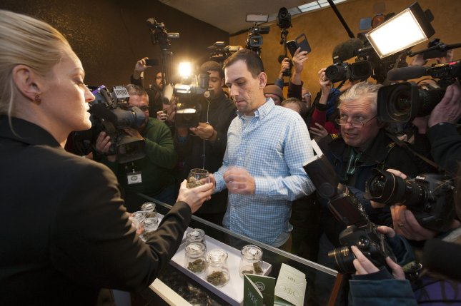 Surrounded by a swarm of media in a small retail marijuana sales room, the first official recreational marijuana purchaser Sean Azzariti of Boston reaches for his first marijuana selection handed over by store owner Toni Fox at the 3D Cannabis Center in Denver on January 1, 2014. Colorado voters approved recreational marijuana use in 2012 with the first retail stores for recreational use opening this morning at 8 A.M.. UPI/Gary C. Caskey