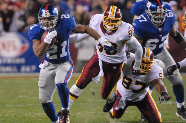 Former New York Giants running back Tiki Barber runs 11 yards for a first down against the Washington Redskins in the second quarter on December 30, 2006 at FedEx Field in Landover, Maryland. File photo by Alexis C. Glenn/UPI