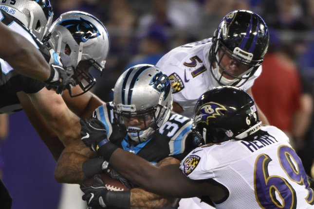 Carolina Panthers running back Brandon Wegher (32) is stopped by Baltimore Ravens defenders Willie Henry (69) and Kamalei Correa (51) in a NFL preseason game at M&T Bank Stadium in Baltimore. File photo by David Tulis/UPI