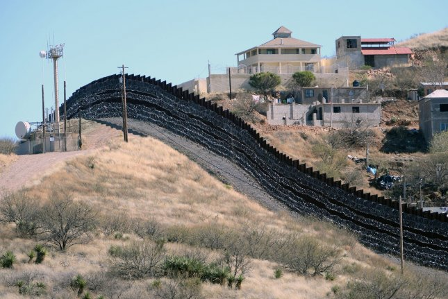 Barbed wire has been placed on the fence along the United States-Mexico border, shown here, heading east from Nogales, Ariz. The U.S. Supreme Court allowed the government to enforce its Remain in Mexico policy for asylum seekers on Wednesday, while lawsuits against the policy work their way through the court system. File Photo by Art Foxall/UPI