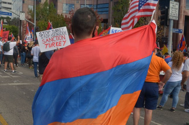 A protester draped in an Armenian flag rallies outside the Azerbaijani Consulate General offices in protest over the conflict between Armenia and Azerbaijan in Los Angeles on November 1, 2020. On September 21 1991, Armenia became the 12th Soviet republic to declare independence. File Photo by Jim Ruymen/UPI