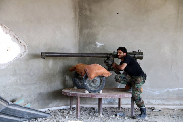 A syrian fighter from the rebel group Free Syrian Army is seen taking a position during fighting with the Syrian regime Army, in Ghouta, Syria, on October 12, 2015. A ceasefire agreement, brokered by U.S. and Russian leaders, took effect at midnight Friday and prohibits fighting between government forces and rebels. The partial ceasefire, though, allows both sides to continue fighting terrorist militants. Photo by Ammar Al Bushy/ UPI