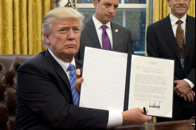 President Donald Trump shows the presidential memorandum withdrawing from the Trans-Pacific Partnership in the Oval Office on Monday. Pool photo by Ron Sachs/UPI