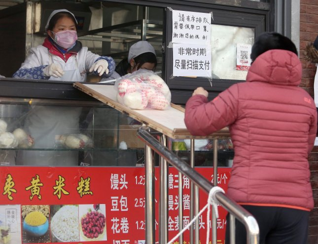 An employee at a Chinese dumpling shop passes orders to waiting customers over a small 'bridge' due to the threat of spreading the deadly coronavirus in Beijing on Monday, February 17, 2020. Photo by Stephen Shaver/UPI