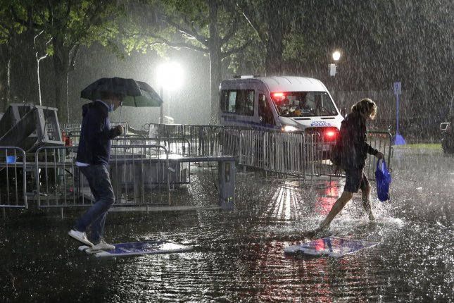Attendees exit the grounds Wednesday during a massive downpour of rain from the remnants of Hurricane Ida at the U.S. Open Tennis Championships at the USTA Billie Jean King National Tennis Center in New York City. Photo by John Angelillo/UPI