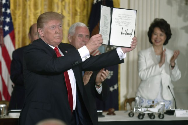 President Donald Trump holds up a Space Policy Directive after a signing ceremony with Vice President Mike Pence (rear) and Transportation Secretary Elaine Chao (R), as he hosts the National Space Council in the East Room of the White House on Monday. Photo by Mike Theiler/UPI